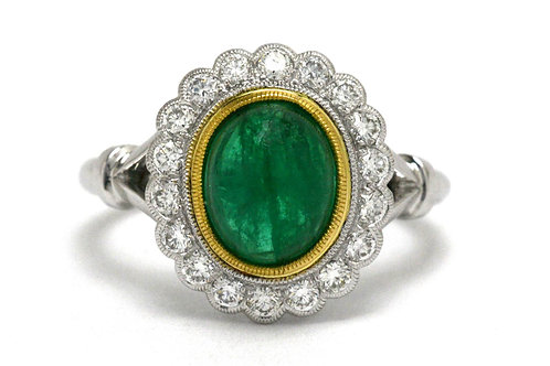 This Princess Diana style antique engagement ring features an oval cabochon emerald surrounded by a halo of diamonds