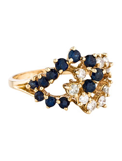 A vintage yellow gold loop ring accented by blue sapphires and diamonds