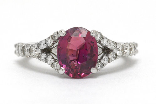 An oval pink sapphire engagement ring with diamonds on the split shank