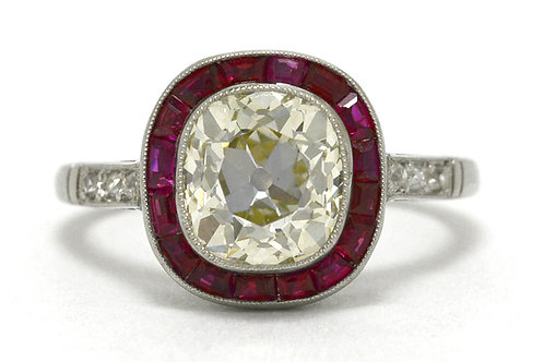 This over 2 carat old mine cushion diamond target ring is surrounded by a halo of rubies