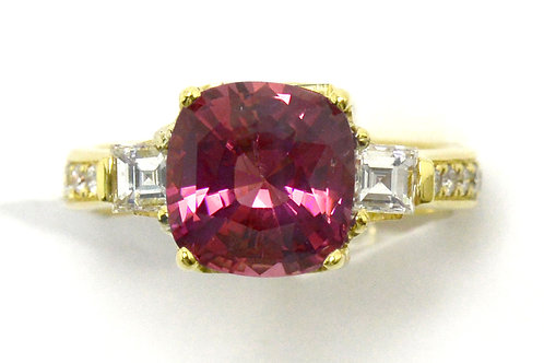 An engagement ring with a cushion pink sapphire and 2 diamonds