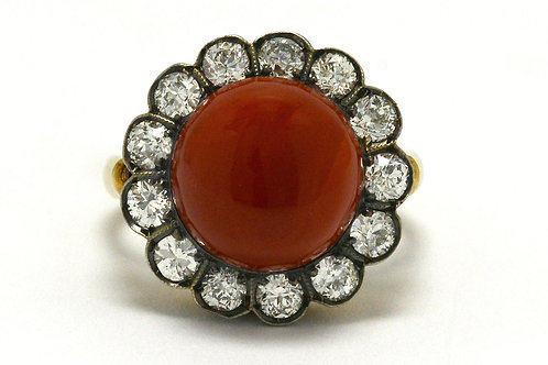 The Buckeye antique cocktail ring features a round cabochon coral accented by a diamond halo