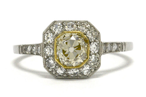 An engagment ring featuring a light yellow old mine cushion center diamond with halo