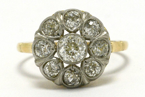 This engagement ring has a diamond halo in a flower cluster design in platinum 18k gold