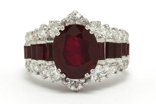 The Anahein cocktail ring has an oval faceted ruby accented by diamonds and rubies