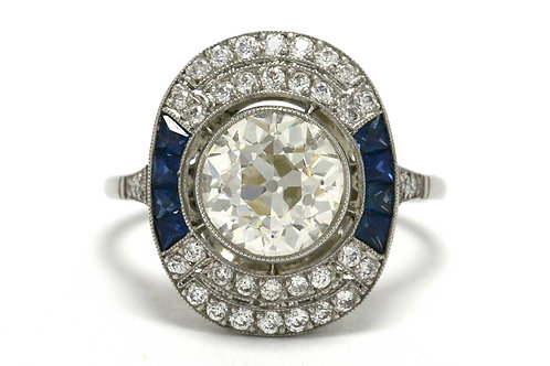 An old mine brilliant diamond surrounded by a blue sapphire gem halo Art Deco engagement ring