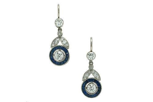 These diamond drop dangle earrings are encircled with blue sapphires