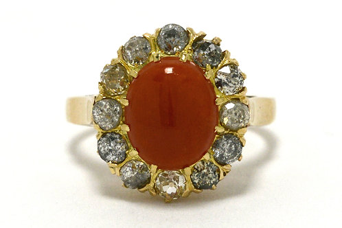 A gold Victorian era coral target engagement ring accented by diamonds