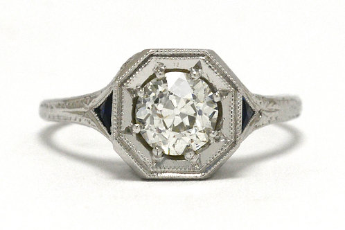 An old european diamond is set amongst 2 triangle blue sapphire in this antique engagement ring