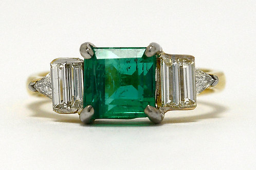 An 18K yellow and white gold engagement ring with a stunning emerald and 2 accent diamonds
