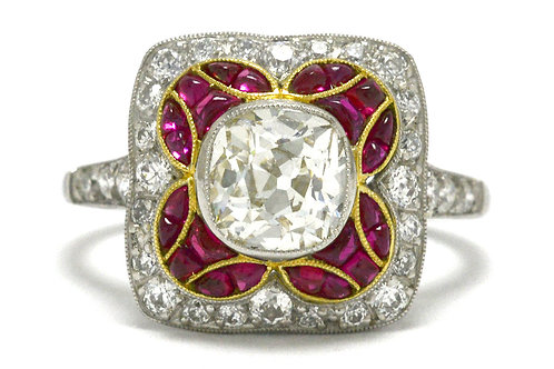 An old mine cushion diamond accented by a ruby halo platinum engagement ring