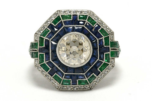 This old European diamond engagement ring is accented by a halo of blue sapphires and emerald