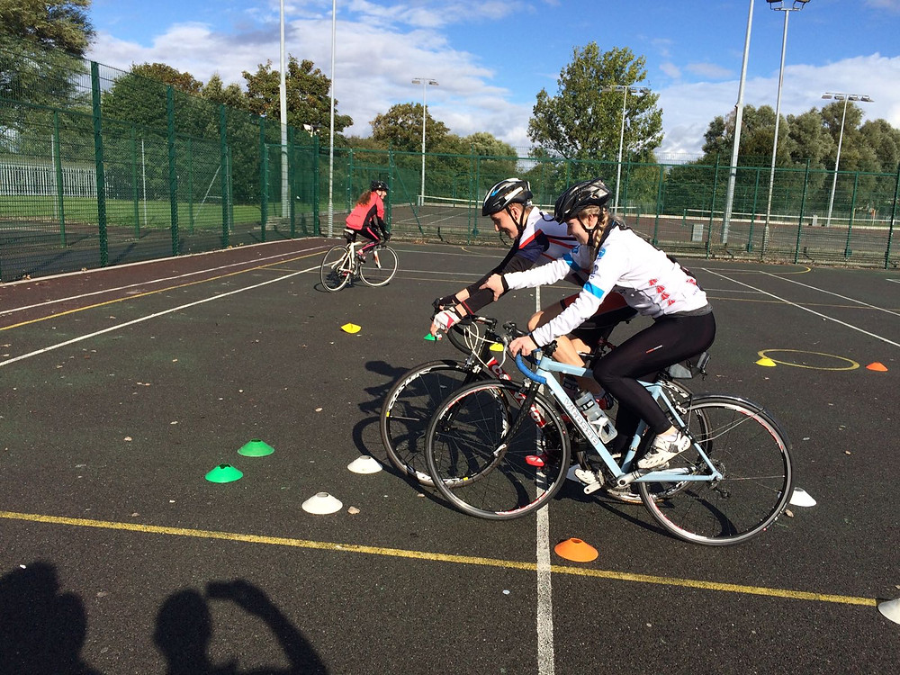 Athletes working with each other to develop bike skills