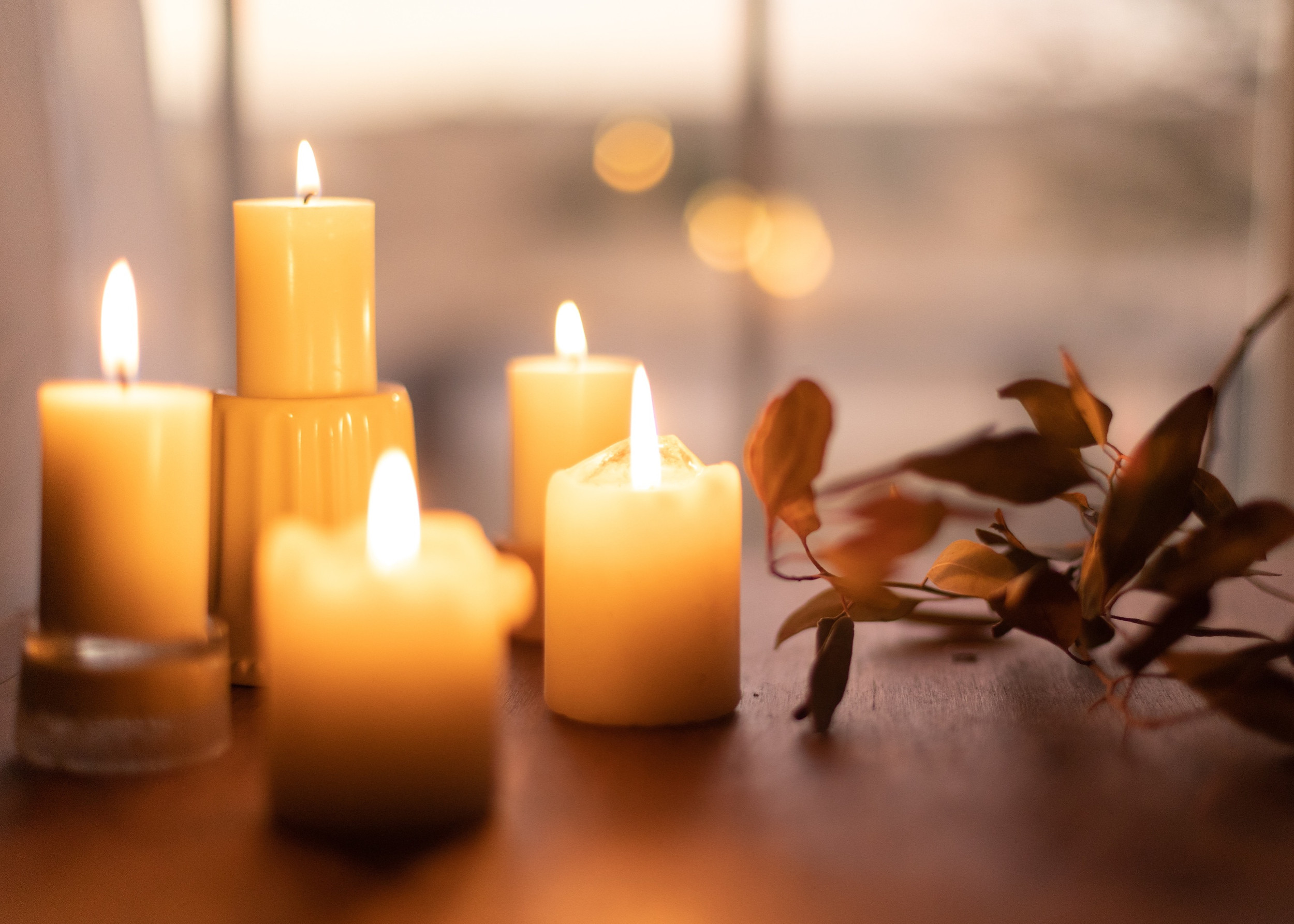 white pillar candles on brown wooden tab