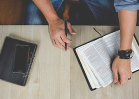 bible man holding Bible and pen on table