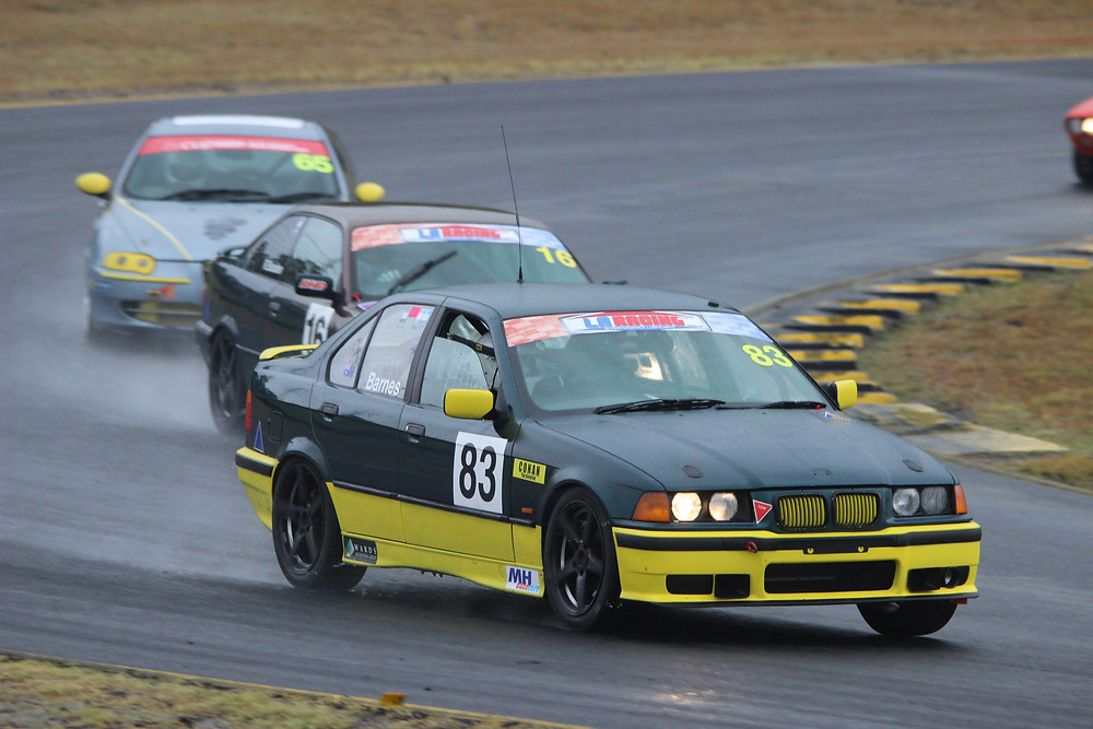 Three cars on track at Sydney Motorsport Park in wet conditions.