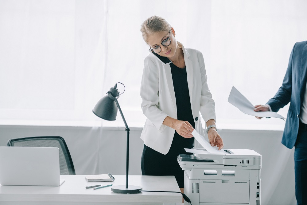 Woman on phone pulling papers off printer