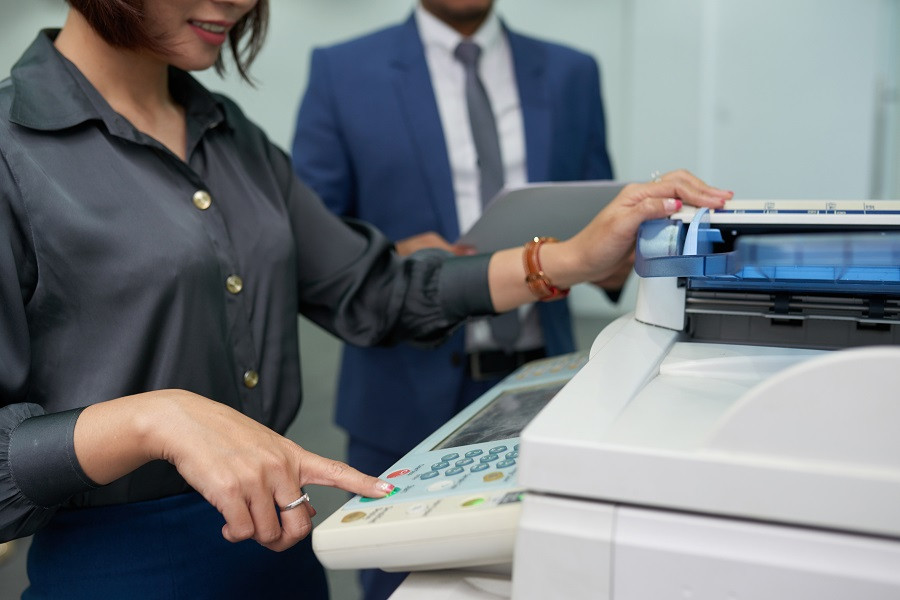 Woman Pressing Button on Office Copier