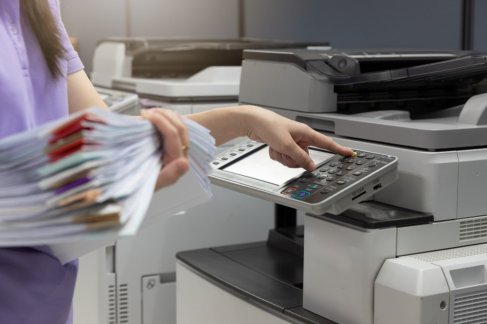Woman Hold a Stack and Papers and Using Printer at Work