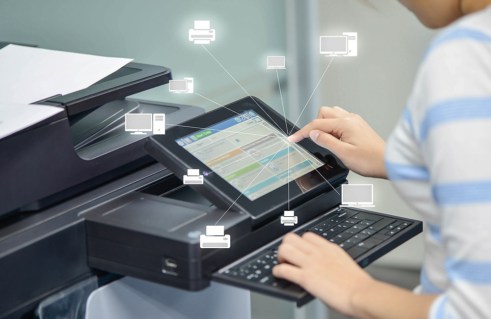 Office worker using screen and keyboard on printer