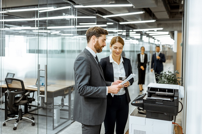 Man and woman standing at office printer