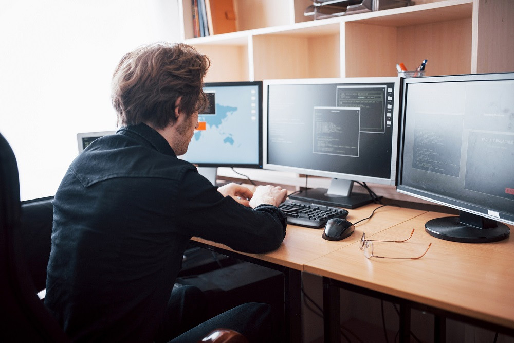 Man with three computer monitors