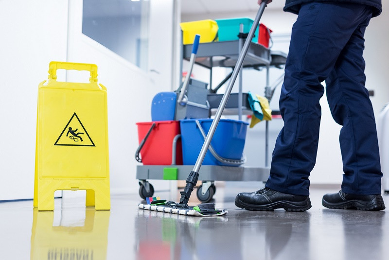 Janitor with Mop and Bucket Standing Next to Slip Caution Sign