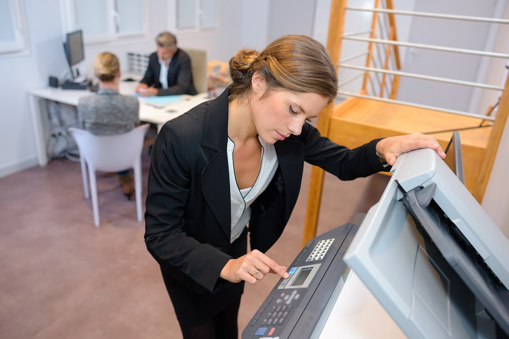 Businesswoman making copies on copier