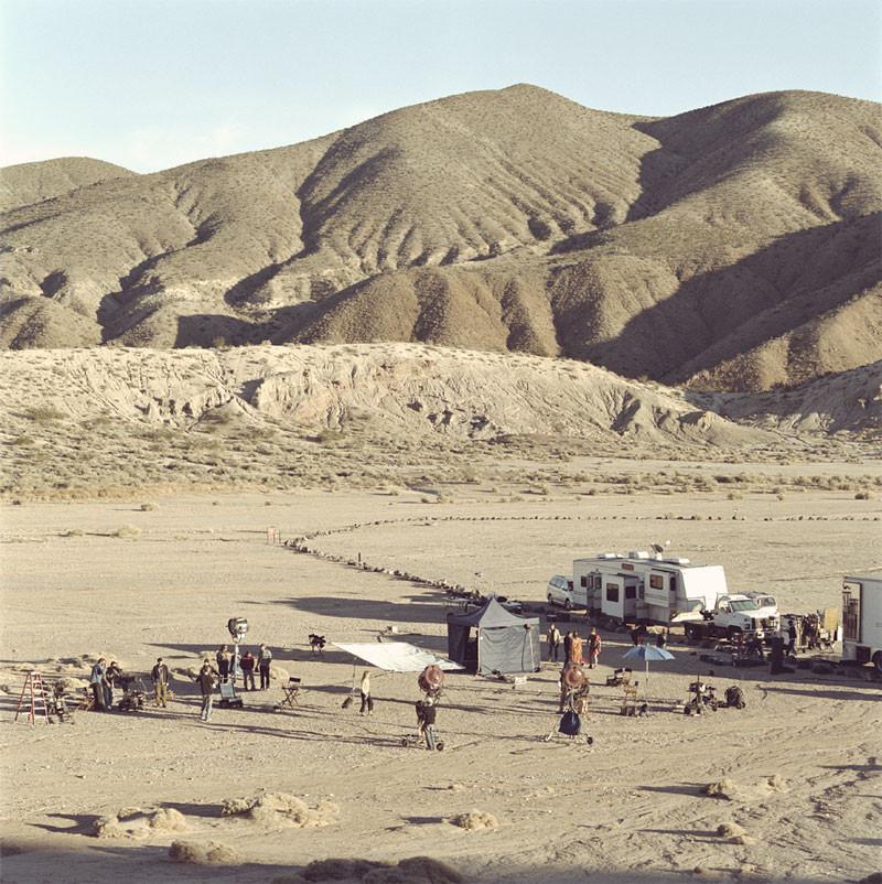 Film shoot in desert with caravan, trucks, tents and equipment