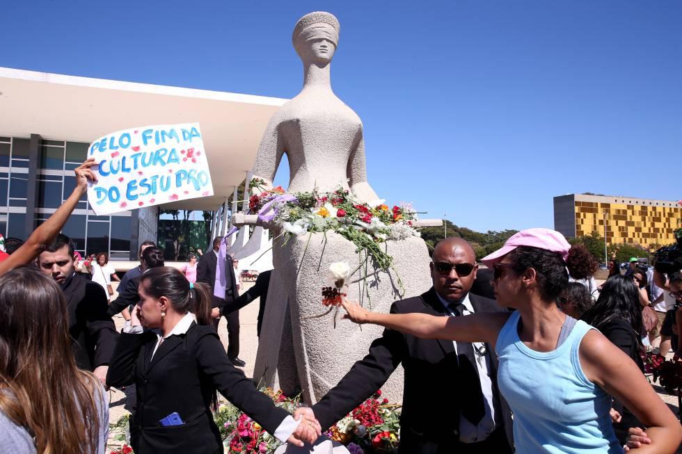 Mulheres protestam depositando flores na estátua da Justiça, em Brasília W.DIAS (AG. BRASIL)