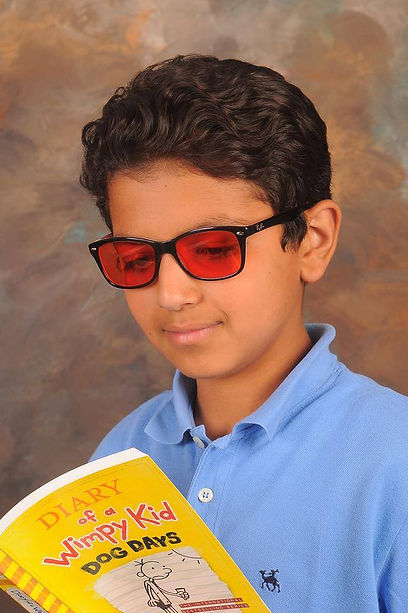 A boy reading a bool while wearing Irlen tinted filters
