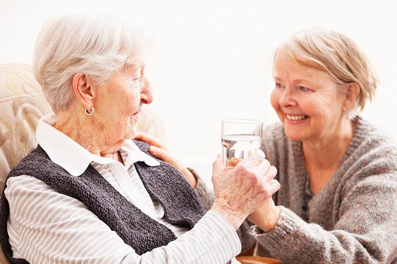 caregiver handing senior woman a glass of water