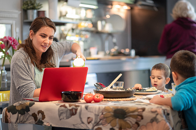 caregiver working and eating with young children