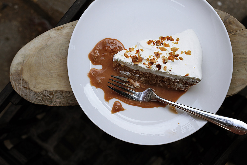 Photograph showing a black of frosting-topped cake and caramel sauce, a fork resting next to them. Photo courtesy of Wix.