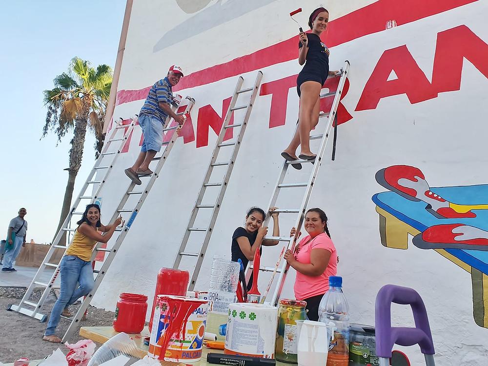 Parte del equipo de voluntariado, subidos a la escalera pintando un mural alusivo al Tran Tran con la Payasa Chanita