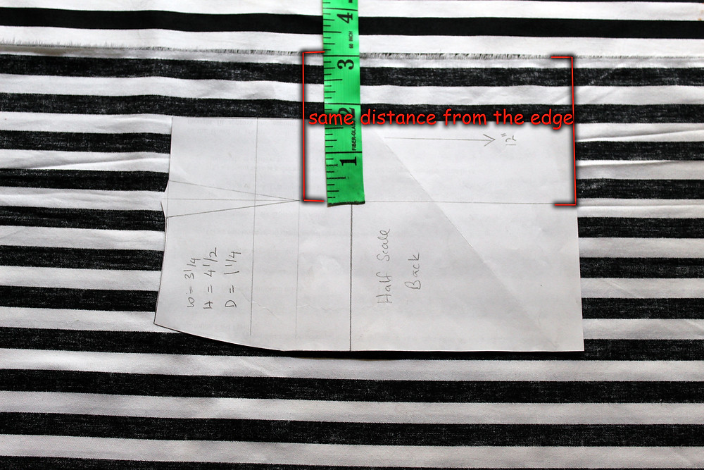 aligning pattern to grain line of fabric with measuring tape