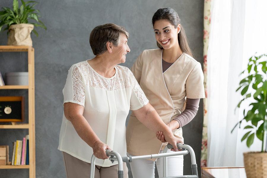 Friendly caregiver supporting a senior p