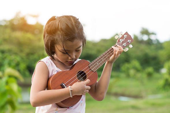 Hawaii child playing ukulele in the garden..jpg