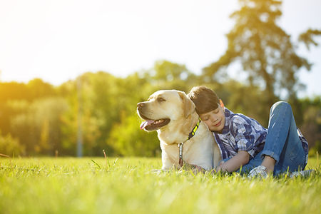 Young boy and his dog lying on the grass