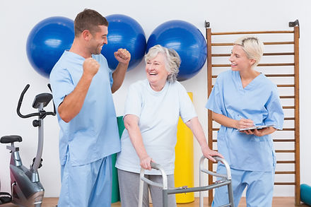 Smiling therapists with invalid woman in