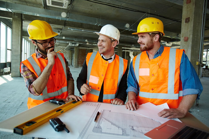 Team of cheerful construction workers di