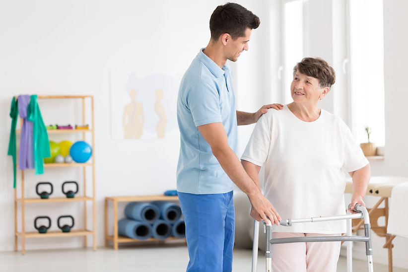 Caring physiotherapist supporting an eld