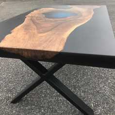 Walnut coffee table with translucent blue epoxy lake incentre and black surround complete with crossbox steel legs.