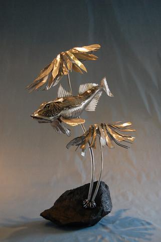 Stainless steel gurnard in kelp sculpture on granite rock base