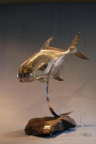 Stainless steel permit fish sculpture on granite rock