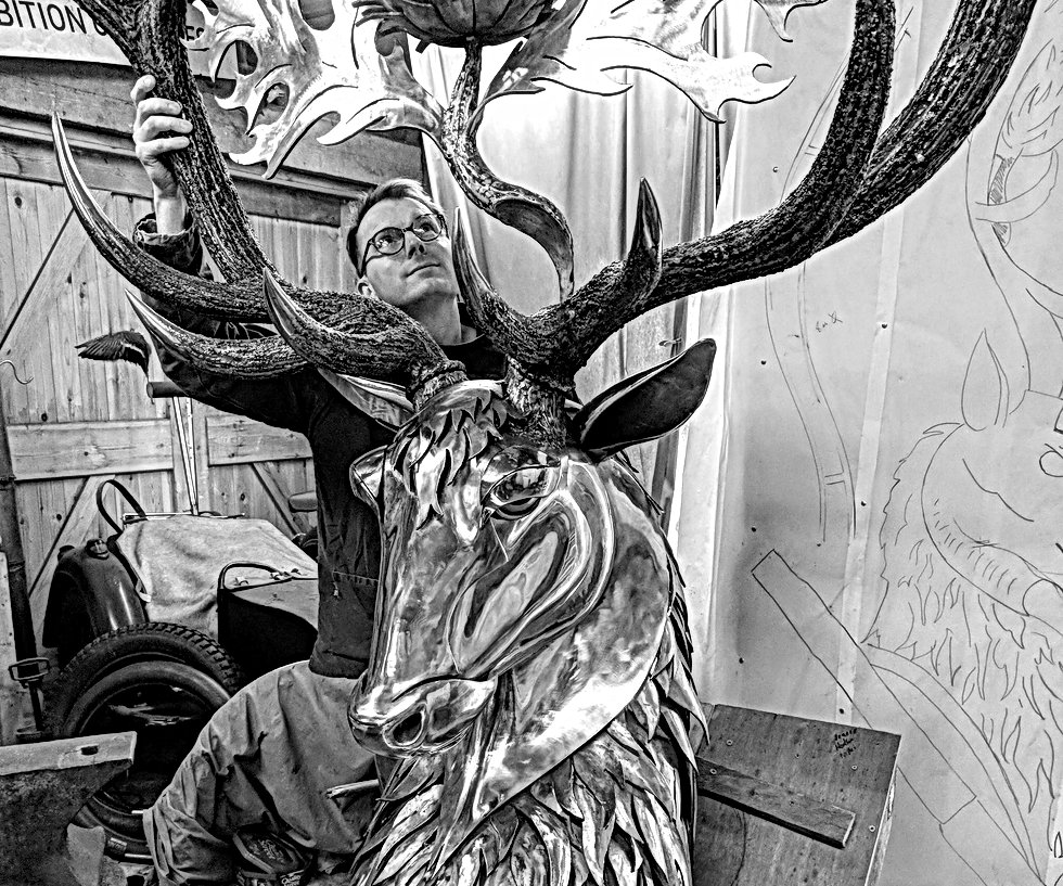 Jason Sweeney sculptor in metal with Highlander Memorial monumental sculpture in his studio. The sculpture is a representation of the highlanders cap badge with stag, thistle and crown. Beaten and welded stainless steel bespoke sculpture commission.