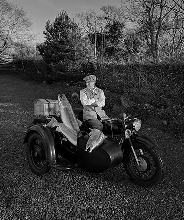 Jason Sweeney, artist and sculptor on motorbike and sidecar with stainles steel salmon commissioned sculpture.
