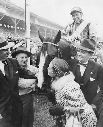 Hasty Road, with John Adams up, gets a kiss from Billie Reuben after his victory in the 1954 Preakness.