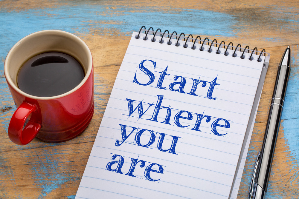 Notepad reading Start wher you are and coffee mug