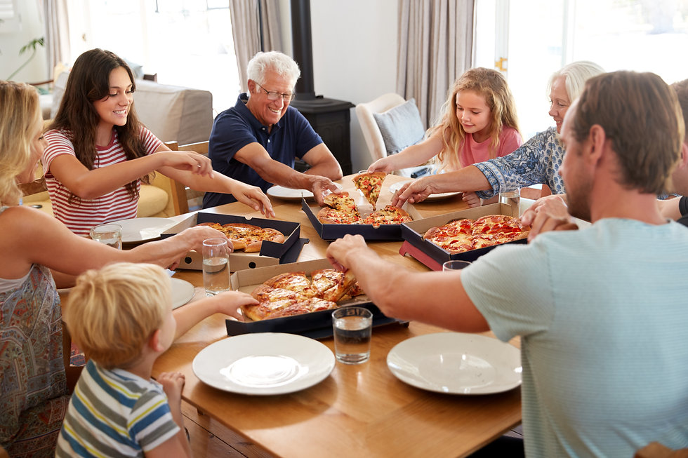Multi Generation Family Sitting Around Table Eating Takeaway Pizza Together.jpg